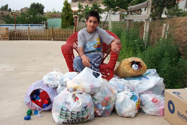 Álvaro en el patio de su casa, rodeado de bolsas de llenas de tapones